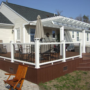 Example of a large classic backyard deck design in Other with a pergola