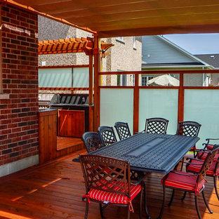 Ejemplo de terraza clásica, de tamaño medio, en patio trasero, con cocina exterior y pérgola