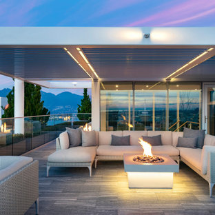 Design ideas for a contemporary deck in Los Angeles with a fire feature and a roof extension.