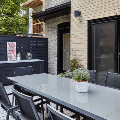 Large minimalist backyard outdoor kitchen deck photo in Toronto with a pergola