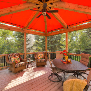 Deck - large transitional backyard deck idea in Minneapolis with a pergola