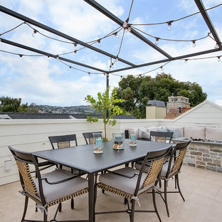 Mid-sized elegant rooftop deck photo in Orange County with a fire pit and a pergola