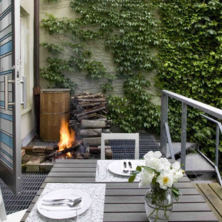 Small trendy backyard deck photo in New York with no cover and a fire pit
