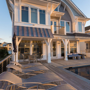 Inspiration for a large coastal backyard outdoor shower deck remodel in New York with a roof extension