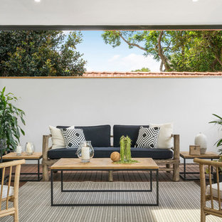 Beach style deck in Sydney with a roof extension.