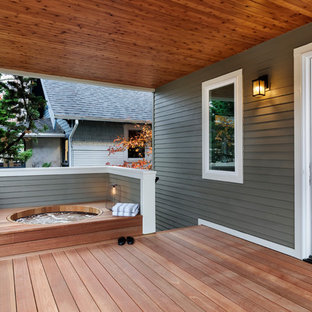 Example of a transitional deck design in Portland with a roof extension