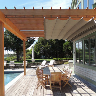 Inspiration for a large coastal backyard deck remodel in Toronto with a pergola