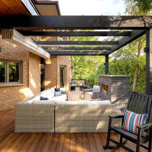 Esempio di una terrazza tradizionale dietro casa con un caminetto e un parasole