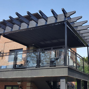 Idee per una grande terrazza industriale dietro casa con una pergola