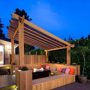 Esempio di una terrazza tradizionale con un focolare e una pergola