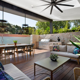 Inspiration for a large contemporary side yard deck in Melbourne with an outdoor kitchen and a roof extension.