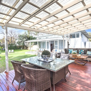 This is an example of a mid-sized contemporary backyard deck in Perth with a pergola.