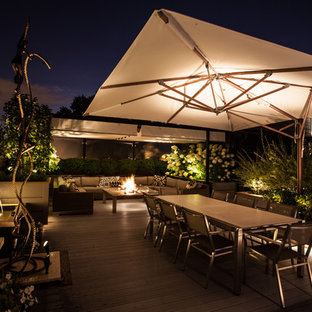 Inspiration for a mid-sized contemporary rooftop deck remodel in Chicago with a fire pit and an awning