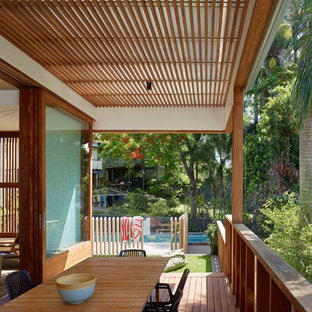 Photo of a mid-sized tropical backyard deck in Brisbane with a roof extension.
