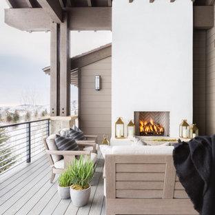 Ispirazione per una terrazza stile rurale con un caminetto e un tetto a sbalzo