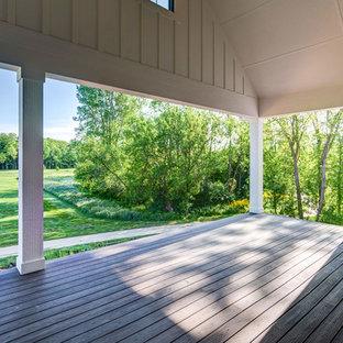 Immagine di grandi terrazze e balconi country dietro casa con un caminetto e un tetto a sbalzo