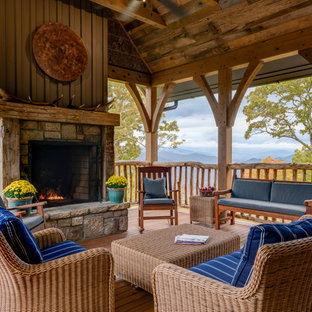 Large mountain style backyard deck photo in Other with a roof extension