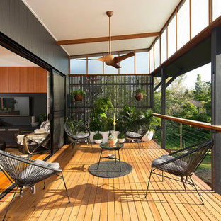 This is an example of a mid-sized contemporary backyard deck in Brisbane with a vertical garden and a roof extension.