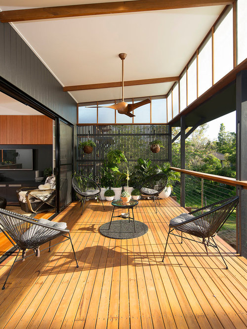 Example Of A Mid Sized Trendy Backyard Deck Design In Brisbane With Roof Extension