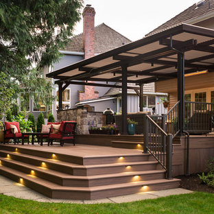 Inspiration for a large transitional backyard outdoor kitchen deck remodel in Seattle with a pergola