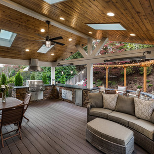 Outdoor kitchen deck - large transitional backyard outdoor kitchen deck idea in Seattle with a roof extension