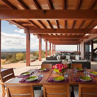 Exemple d'une grande terrasse arrière sud-ouest américain avec un point d'eau et une pergola.