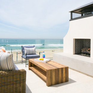 Example of a large beach style deck design in Orange County with a fire pit and no cover