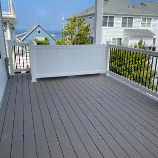 Aménagement d'une grande terrasse arrière bord de mer avec jupe de finition et une extension de toiture.