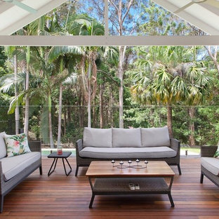 Photo of a transitional backyard deck in Sunshine Coast with a roof extension.