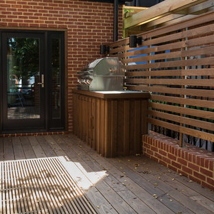 Outdoor kitchen deck - small modern side yard outdoor kitchen deck idea in Baltimore with no cover