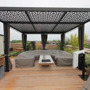 Esempio di una grande terrazza design sul tetto con una pergola