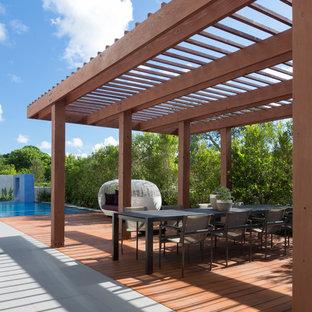 Esempio di una terrazza design di medie dimensioni e dietro casa con fontane e una pergola