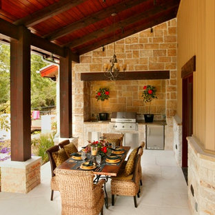 Example of a farmhouse backyard outdoor kitchen deck design in Austin with a roof extension