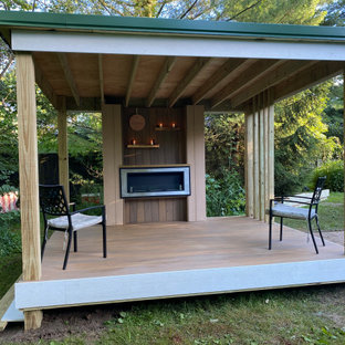 Small minimalist backyard privacy deck photo in Other with a roof extension