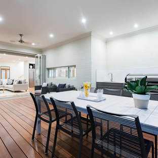 Outdoor kitchen deck - large scandinavian side yard outdoor kitchen deck idea in Canberra - Queanbeyan with a roof extension
