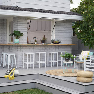This is an example of a mid-sized modern backyard deck in Sydney with an outdoor kitchen and no cover.