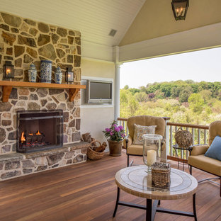 Elegant backyard deck photo in Philadelphia with a fire pit and a roof extension