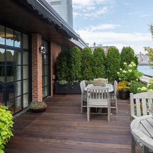 Elegant rooftop deck container garden photo in New York with an awning