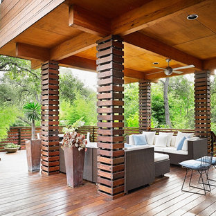 Example of a mid-sized zen backyard deck design in Austin with a roof extension