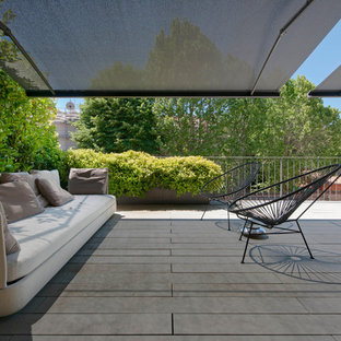 Expansive modern roof terrace and balcony in Bologna with an awning.