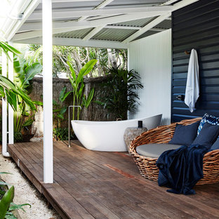 Photo of a mid-sized tropical backyard deck in Sydney with an outdoor shower and a roof extension.