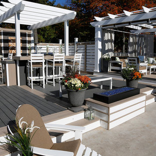 Large beach style courtyard deck photo in Toronto with a pergola