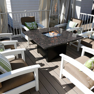 Example of a large beach style courtyard deck design in Toronto with a pergola
