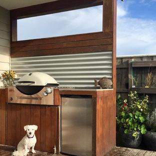 Exemple d'une terrasse avec une cuisine extérieure arrière bord de mer de taille moyenne avec une extension de toiture.