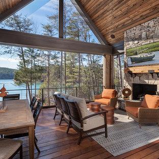 Ispirazione per una terrazza stile rurale con un focolare e un tetto a sbalzo