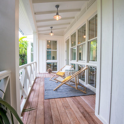 Example of a mid-sized beach style deck design in Tampa with a roof extension