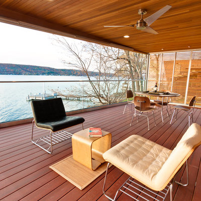 Example of a large minimalist deck design in New York with a roof extension