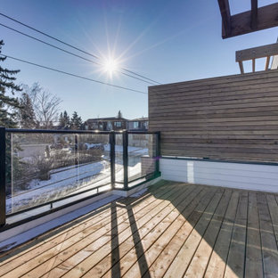Trendy rooftop privacy deck photo in Calgary with a pergola