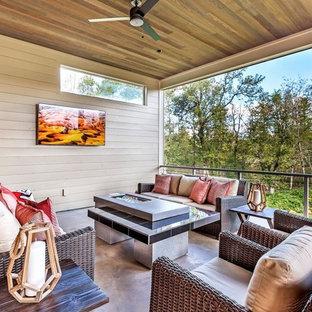 Aménagement d'une grande terrasse et balcon arrière industrielle avec un foyer extérieur et une extension de toiture.