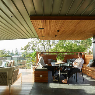 Photo of a contemporary deck in Brisbane with a roof extension.